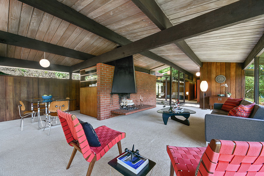 living room with mid century moderm furniture and a brick fireplace wall
