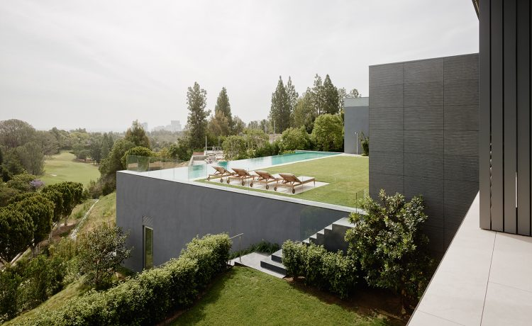 In the backyard, flower gardens bloom below spectacular views of LA and an infinity pool that faces downtown