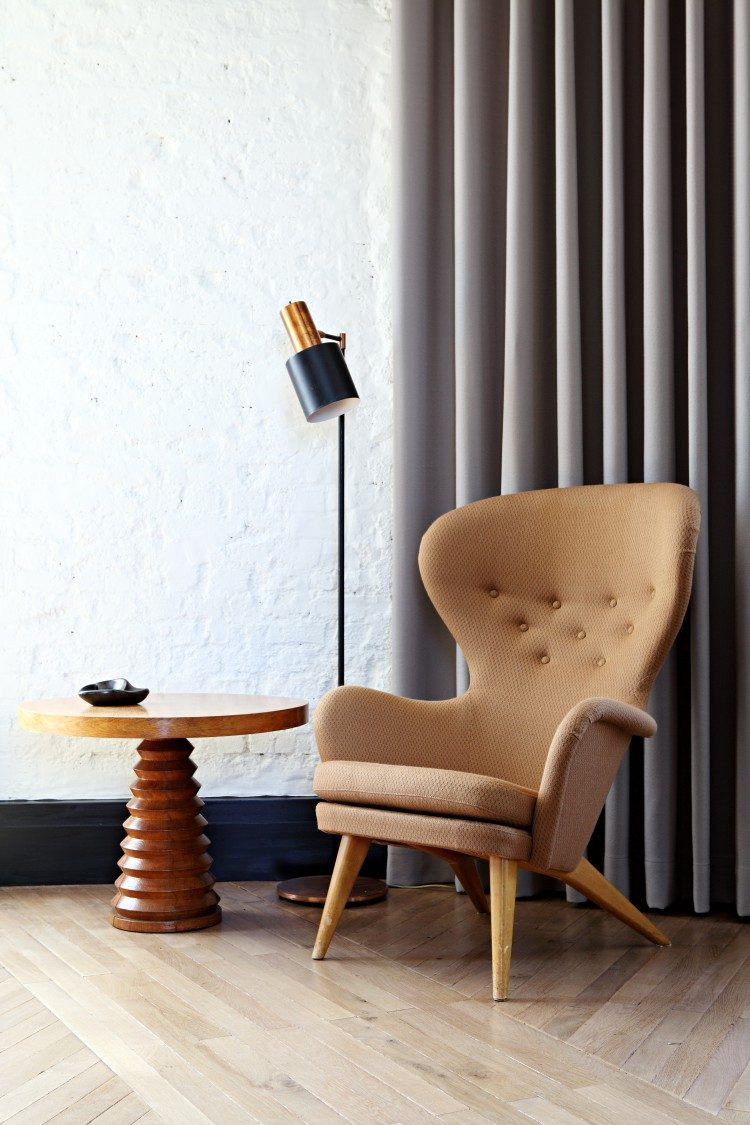 reading space with a mid-century modern chair and a wooden table
