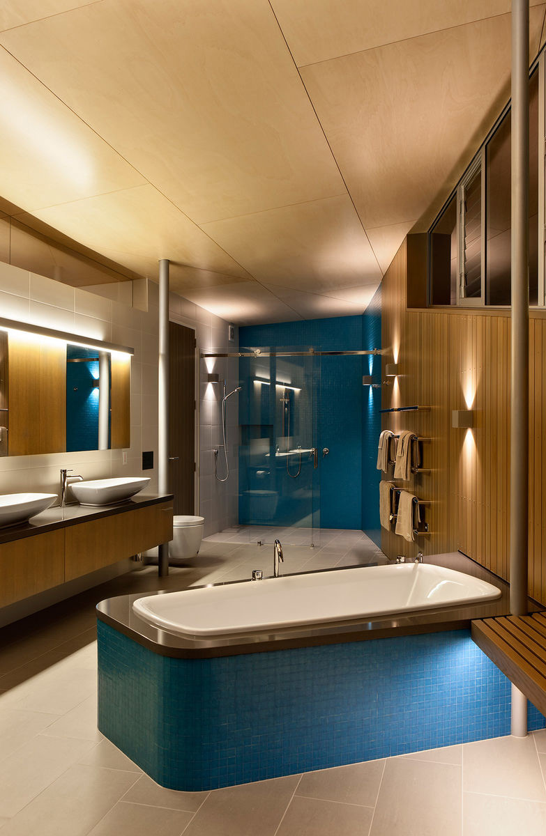 The bathroom is also clad with wood but also with blue tiles