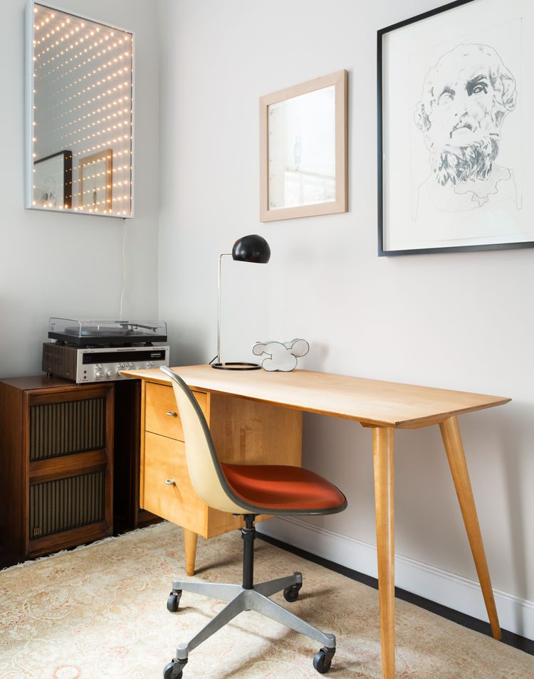 mid century modern home office is decorated with unique lighted mirror