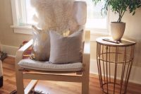 04 off-white Poang chair with pillows and a fur cover for a living room
