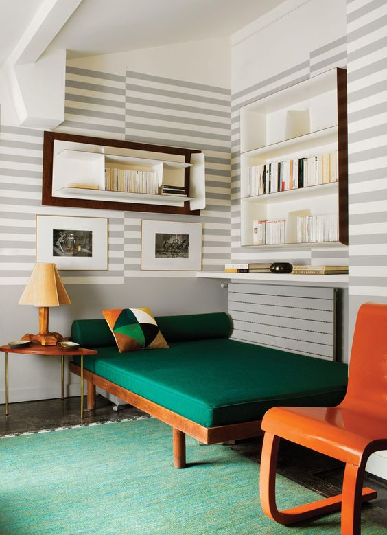 Striped walls and a bold green couch