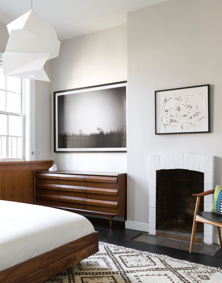 artworks and a fireplace give the bedroom an original look