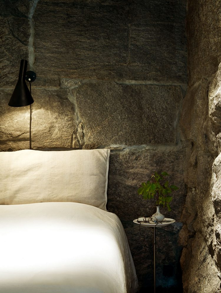 The rough stone walls here look somewhat cozy, which is unexpected, the secret is in soft textures of the bedding and a cute lamp.