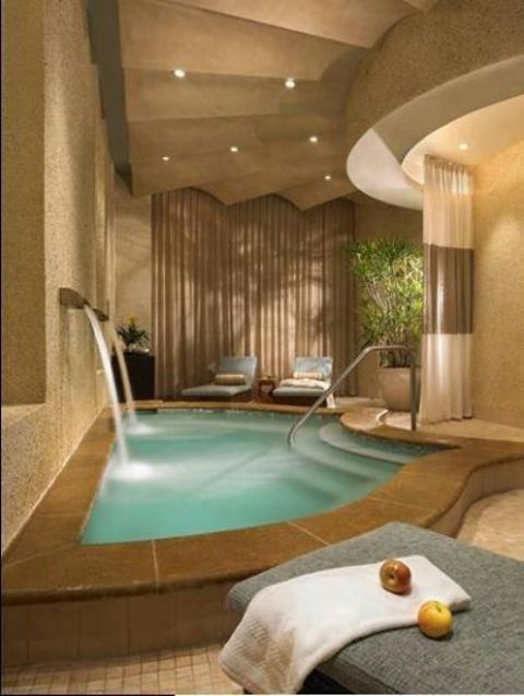 tiny indoor pool with two waterfalls and a tiled deck