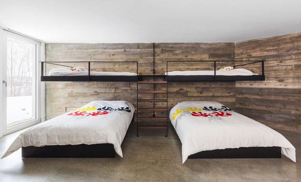 Reclaimed wood and earthy colored concrete floor make this bedroom cozier