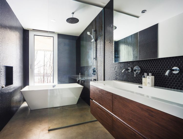 The bathroom is decorated in dark colors with the same black mosaic tiles as in the kitchen