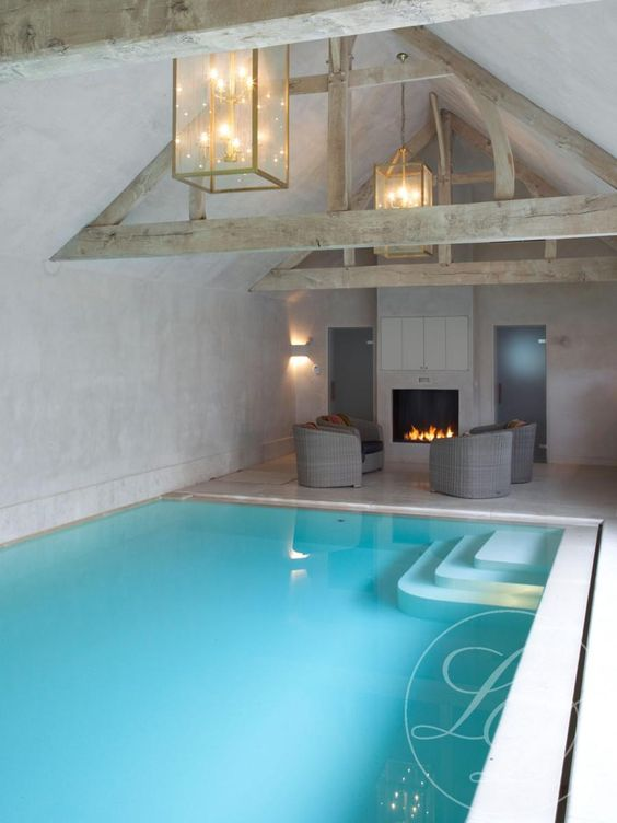 blue indoor pool with a poolside fireplace and chairs