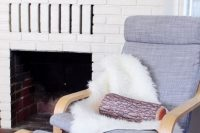 13 grey Poang chair with faux sheepskin and a log pillow