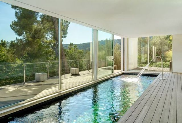 long and narrow indoor pool with a wooden deck and views