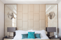 19 symmetrical mirrors with a leather headboard in-between