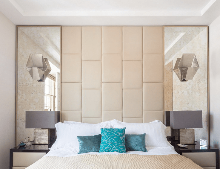 symmetrical mirrors with a leather headboard in-between