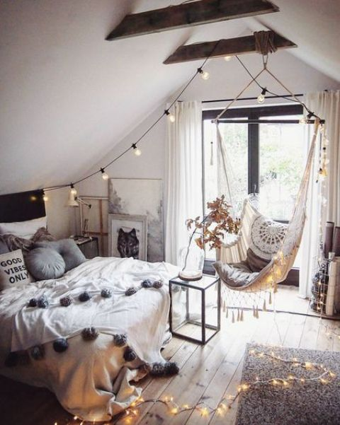a boho attic teen room with a bed, a suspended chair, lights and lots of artworks is a lovely space to be