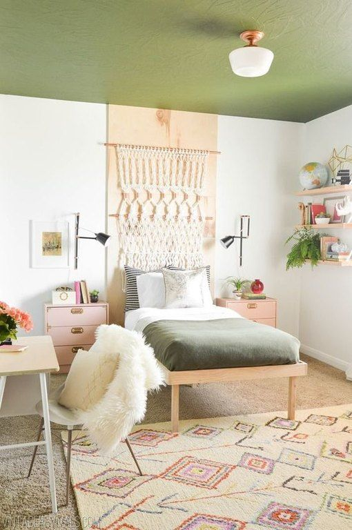 a boho teen room with a green ceiling, a macrame hanging, floating shelves, pink nightstands and a tiny desk and a chair
