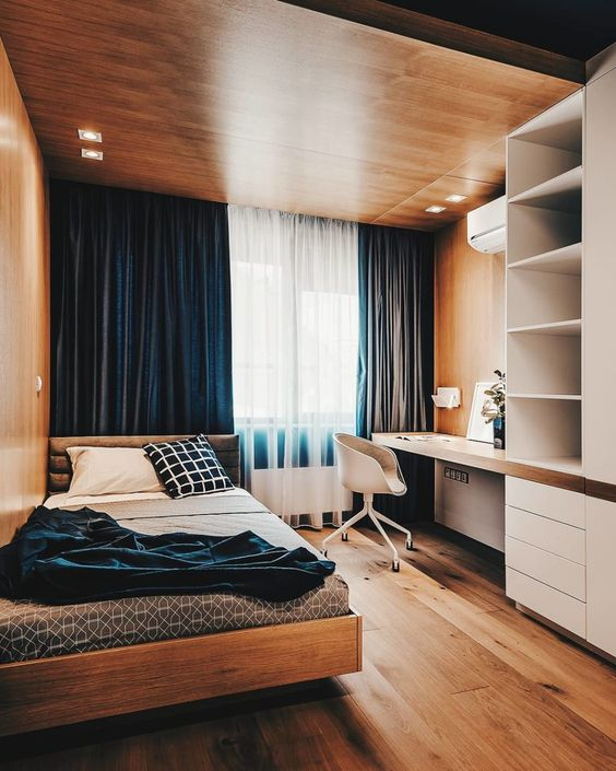 a bold minimalist teen room with a wooden ceiling with lights, navy curtains, a storage unit with a built-in desk, a comfy bed and blue bedding