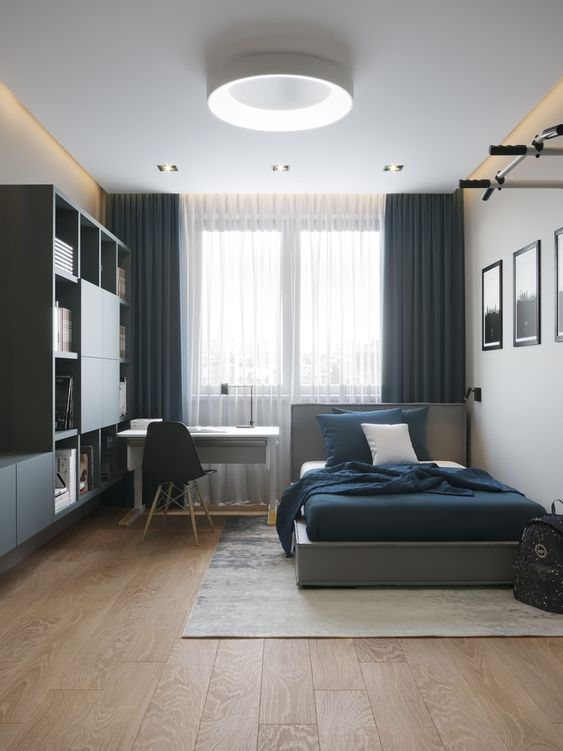 a chic contemporary teen room with a large storage unit taking one wall, a small desk and a comfy bed, a gallery wall and blue curtains