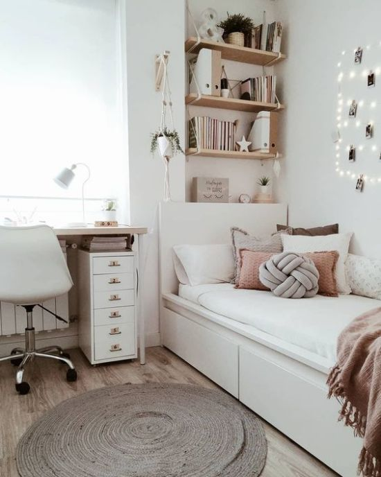 a chic neutral teen room with wall-mounted shelves, a comfy white bed with lots of pillows, a desk and a white chair plus potted plants