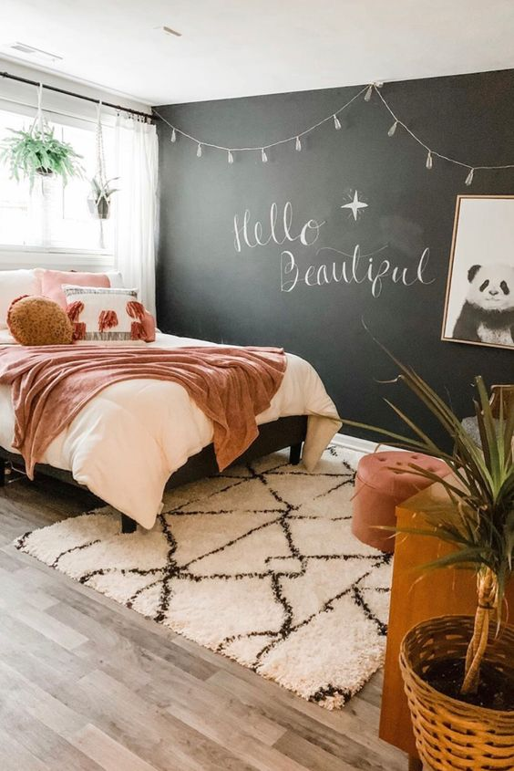 a chic teen bedroom with a chalkboard wall, a bed with pretty pink bedding, a wooden desk, a chair and a footrest