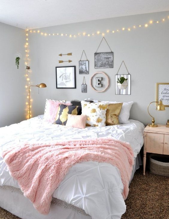 a chic teen girl bedroom with grey walls, a large bed with printed pillows, a lovely gallery wall and lights over the bed