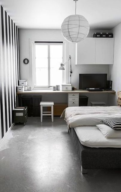 a conemporary teen room with a study space by the window, a windowsill desk, a cabinet, a bblack bed and a striped accent wall