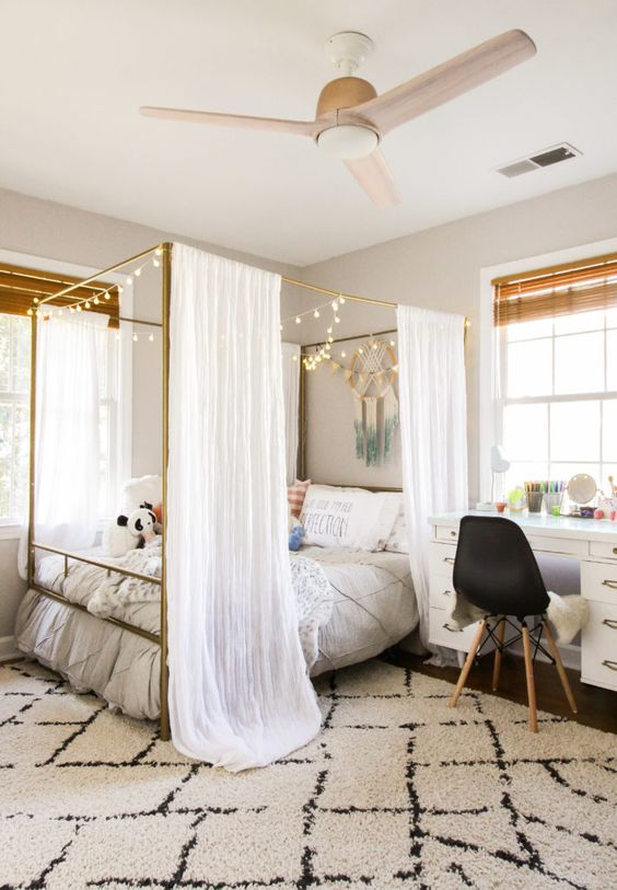 a cool teen room with a large canopy bed with lights, a white desk, a black chair and shades is a pretty space