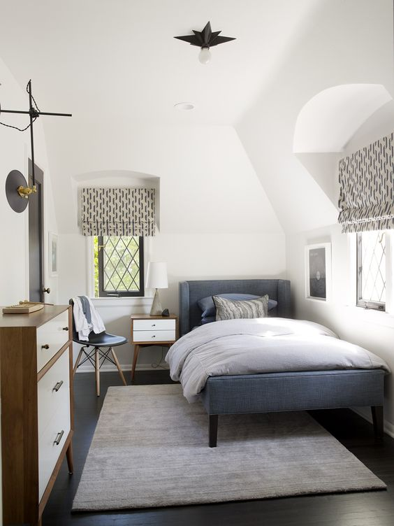 a cozy mid-century modern teen room with a blue upholstered bed, a dresser, printed textiles, a small nightstand and a chair