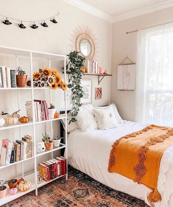 a lovely teen room with a black bed, a large open storage shelf with blooms and pumpkins, a shelf and a mirror over the bed