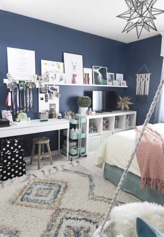 a lovely teen room with navy walls, a turquoise bed, neutral and pastel bedding, a white desk or makeup vanity, a storage unit and a ledge gallery wlal