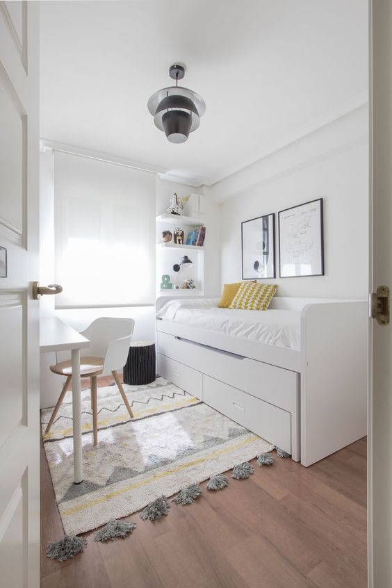 a neutral Scandinavian bedroom with a bed with storage, a desk and a chair, built in shelves and a printed rug