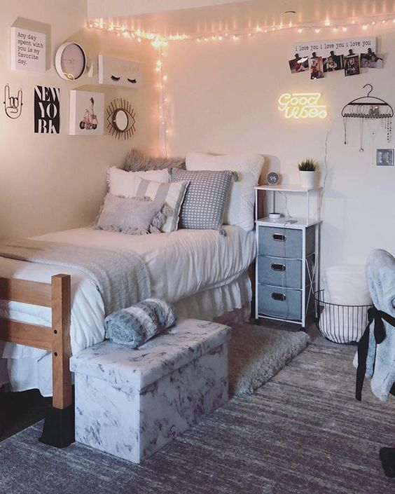 a neutral teen bedroom with a bed, a small storage nightstand, some lights and a pretty gallery wall plus a floral box for storage