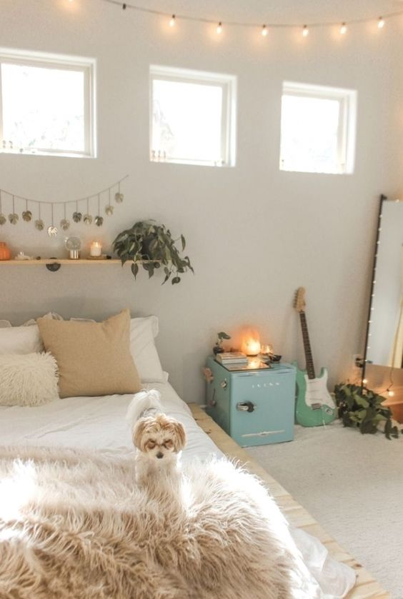 a neutral teen bedroom with neutral walls, a pallet bed, a floor mirror, a blue storage cabinet, a floating shelf with greenery and candles and a guitar