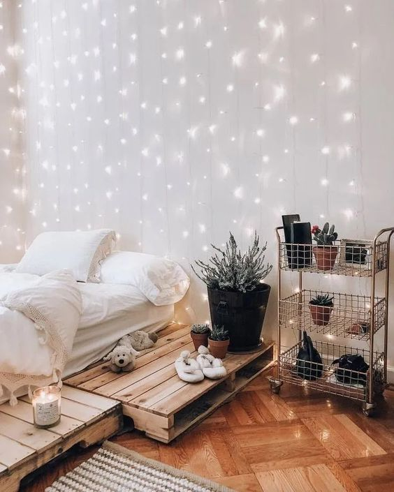 a relaxed boho teen bedroom with a pallet bed, a metal layered shelf, neutral bedding, potted plants