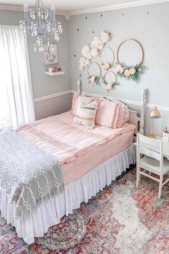 a romantic vintage teen bedroom with light blue walls, vintage neutral furniture, wreaths with blooms, a blue crystal chandelier and pastel bedding