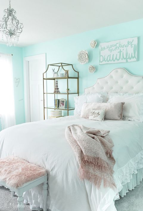 a romantic vintage teen room with mint blue walls, a tufted white bed, a refined storage shelf, some faux blooms and a crystal chandelier
