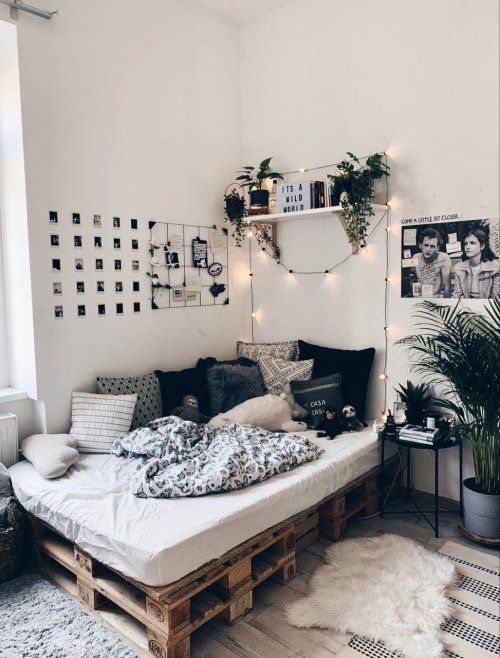 a simple and cool boho teen bedroom with a pallet bed, potted plants, a gallery wall and a grid, printed pillows and lights over the bed