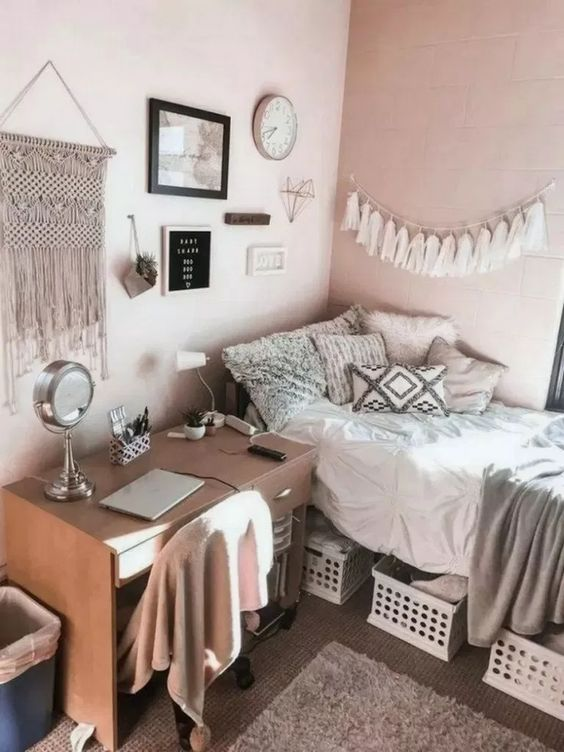 a simple teen boho room with a bed and a desk, boxes for storage, a gallery wall with tassels and macrame is cool