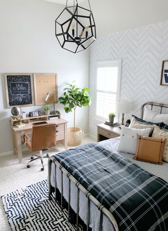 a stylish farmhouse teen room with a metal bed, lots of pillows, a small desk and a leather chair plus a faceted pendant lamp