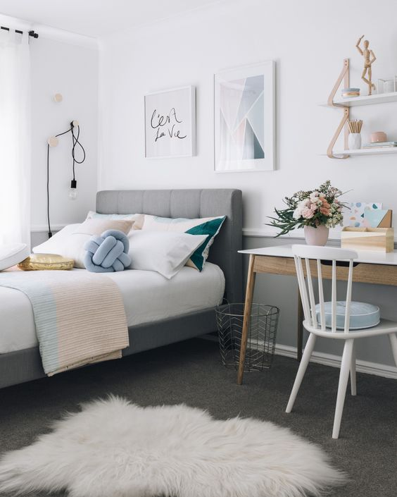 a stylish modern teen bedroom with a grey upholstered bed, pastel and color block bedding, a desk and a chair, some shelves and cool art