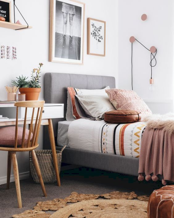 a stylish modern teen room with an upholstered bed, a white desk, a wooden chair, a gallery wall and cool hooks