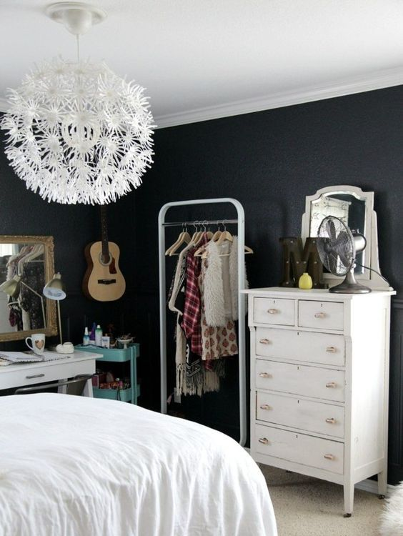 a stylish teen room with black walls, a dresser, a makeshift closet, a white desk, a turquoise storage cart and a floral chandelier