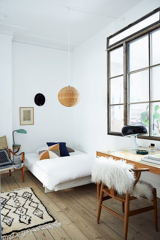 a teen Scandinavian room with a small bed, a desk and a chair, a rattan pendant lamp and a large window with no curtains
