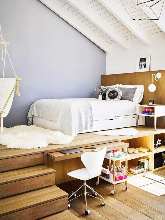 a teen room with a raised platform bed, a built-in desk and storage compartments, a white chair and a suspended chair