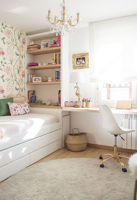 an airy teen room with floral wallpaper, built-in shelves, a windowsill desk, a white chair and a crystal chandelier