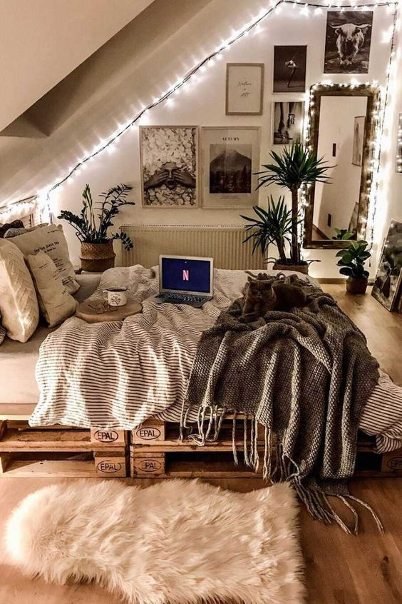 an attic teen room with a pallet bed with pretty bedding, a black and white gallery wall, a mirror and lots of lights and potted greenery