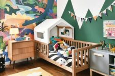 a bright and fun jungle-themed kids' bedroom with a bold artwork, a house bed and colorful jungle-inspired toys