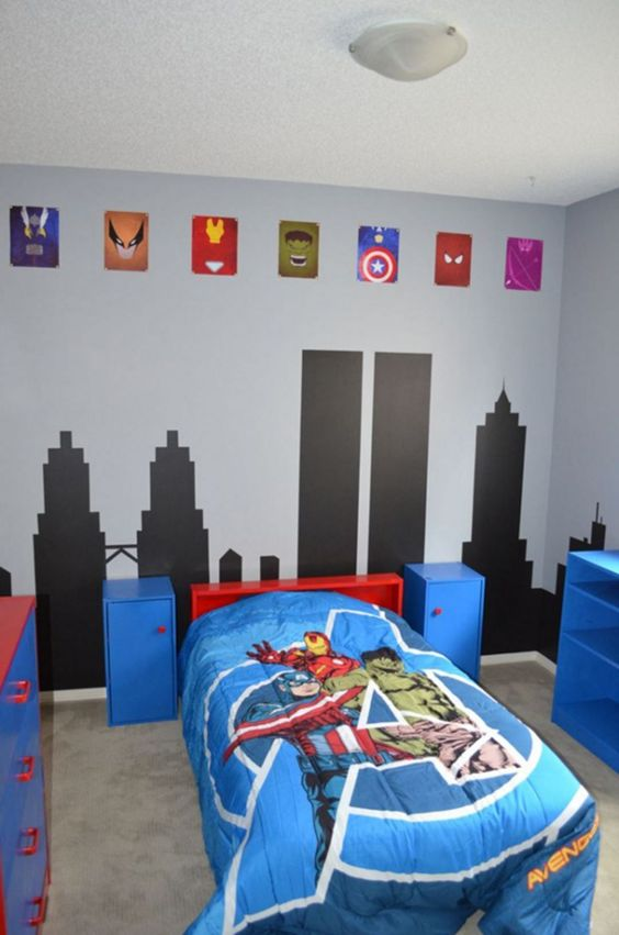 a colorful Marvel super hero themed kids' room done in blue, red and black, with emblems and bright bedding