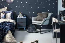 a cool space-themed kid's room done in navy, grey and white, with a star pattern incorporated and blue and grey furniture