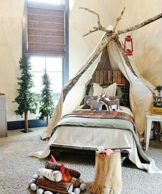 a gorgeous camp-themed kids' room with canopy on branches, woven shades, faux trees and a faux fireplace