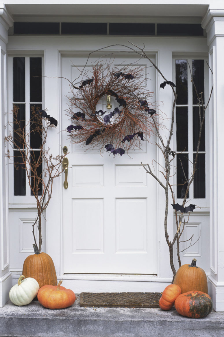 Hang a rustic spooky wreath on your front door. Vines and black bats' silhouettes would do the job.
